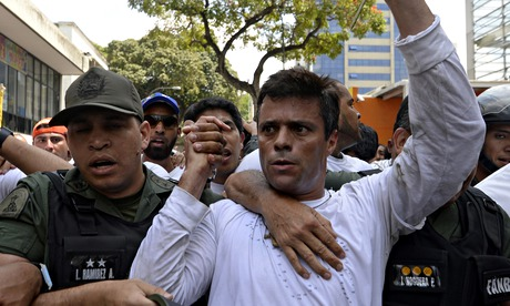 Leopoldo Lopez is escorted by members of the National Guard after surrendering in Caracas.